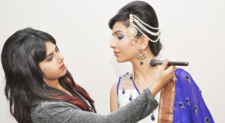 Elisha is doing makeup & hair on a model.